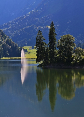glarus: Summer scene in the Swiss Alps. Travel destination lake Obersee. Firs and fountain.