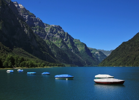 glarus: Boats on lake Klontal. Mt Glarnisch. Summer scene in the Swiss Alps