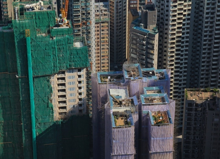 scaffolds: Construction site with scaffolds made of bamboo. Rooftop gardens. Scene in the centre of Hong Kong. Dense architecture.
