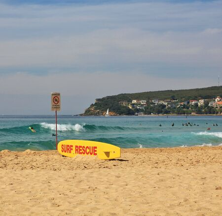 swell: Popular beach in Sydney. Livesaving surfboard on the shore.