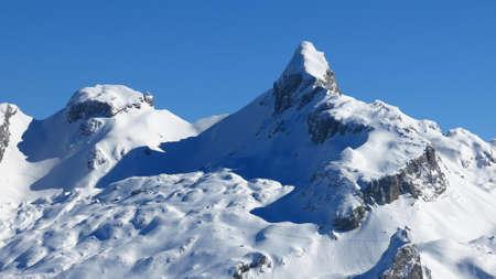 Snow covered mountains in the Swiss Alps. View from Mt Klingenstock. Peak of Mt Chronenstock. Stock Photo