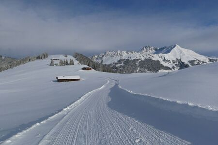 saanenland: Snow covered mountains in Gstaad and winter hiking path on Mt Wilspile.