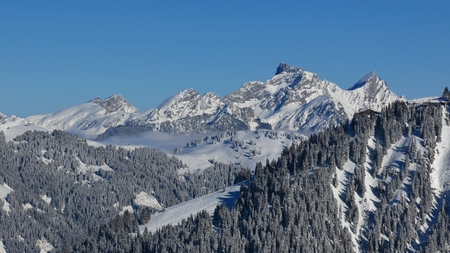 saanenland: Winter scene in Gstaad. View from Mt Wispile. Wasserngrat and distant view of Mt Spillgerten. Stock Photo
