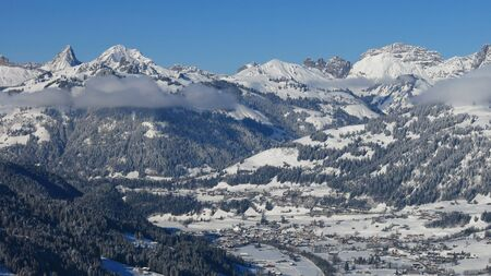 saanenland: Village Saanen and snow covered mountains. Winter scene in the Swiss Alps.