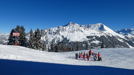 Winter scene in Gstaad. Ski slope on top of Mt Wispile. Snow covered Mt Lauenenhorn. Stock Photo