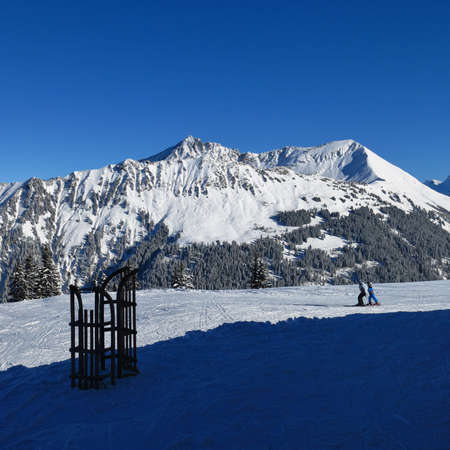gstaad: View from the top of Mt Wispile. Mt Lauenenhorn. Sledge and skier. Winter scene in Gstaad, Swiss Alps.
