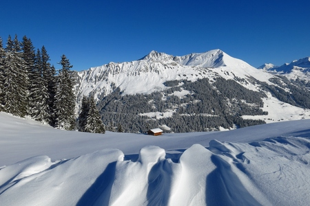 Landscape in Gstaad, Swiss Alps. Snow shaped by wind and Mt Lauenenhorn. Firs.