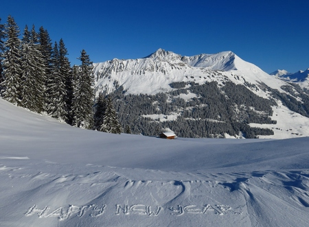 wintery: Wintery landscape in Gstaad, Swiss Alps. Happy new year wish engraved in snow. Mt Lauenenhorn.