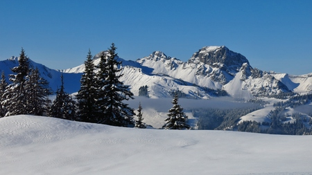 View from Mt Hohe Wispile, Gstaad. Wintery landscape. Snow covered Mt Videmanette. Winter scene in the Swiss Alps.