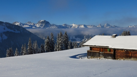 Winter scene near Gstaad, Swiss Alps. Snow covered mountains and forest. Old timber hut. Stock Photo