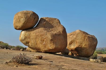 Big granite boulder with smaler boulder on top. Popular boulder for rock climbing. Sculpture shaped by mother nature. Scene in Hampi, India.