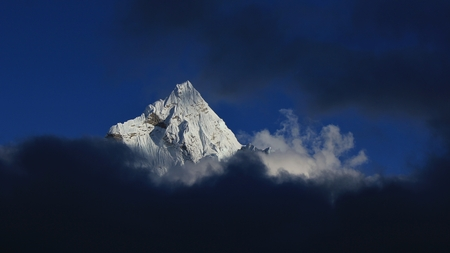Peak of mount Ama Dablam reaching out of dark clouds.