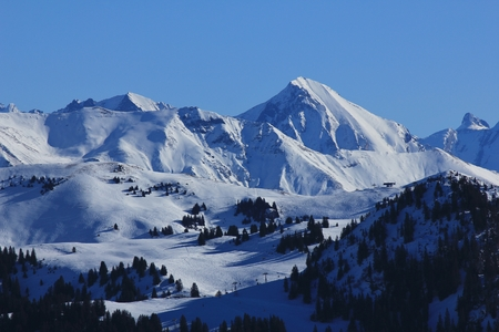 Ski slopes in the Bernese Oberland, Switzerland. View from the Rellerli ski area. View of the Saanersloch ski slopes and snow covered mountains.