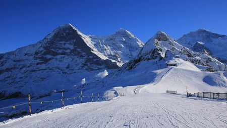 monch: Winter scene in Grindelwald. Ski slope and snow covered mountaind Eiger, Monch, Lauberhorn and Jungfrau. Stock Photo