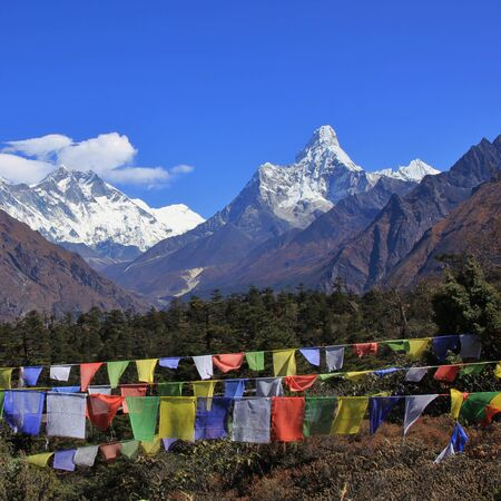 sherpa: Autumn day in the Everest National Park. Snow capped mountains Lhotse and Ama Dablam. Prayer flags.