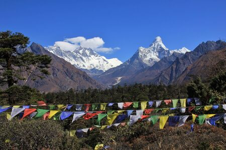 sherpa: Scene near Khumjung, Everest National Park, Nepal. Prayer flags and snow capped mountains Lhotse and Ama Dablam. Stock Photo