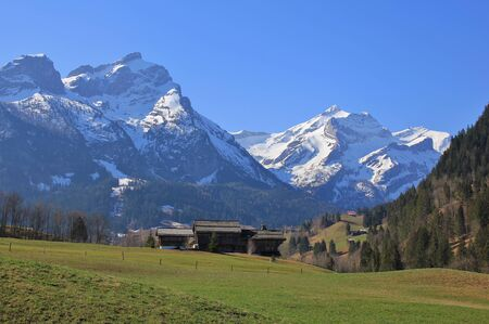 Spring day in the Bernese Oberland. Snow capped mountains Schlauchhorn and Oldenhorn. Landscape in Gsteig bei Gstaad, Switzerland.