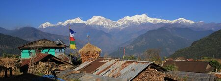 View from a village near Ghale Gaun, Annapurna Conservation Area, Nepal. Snow capped Manaslu range. Corn on the cob stored next to a farmhouse.