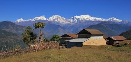 Houses near Ghale Gaun and snow capped Manaslu range. Rural scene in Nepal. Stock Photo