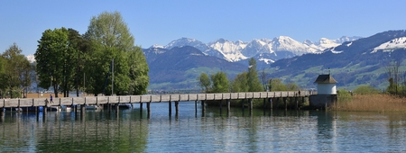 Timber gangplank in Rapperswil. Lake Zurichsee and snow capped mountains. Spring scene in Switzerland.