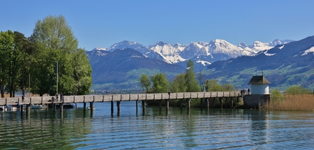 Springtime in Rapperswil. Gangplank on lake Zurichsee. Green trees and snow capped mountains.