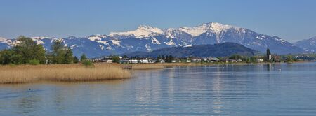 Shore of lake Zurichsee and snow capped mountain Grosser Speer. View from Rapperswil.