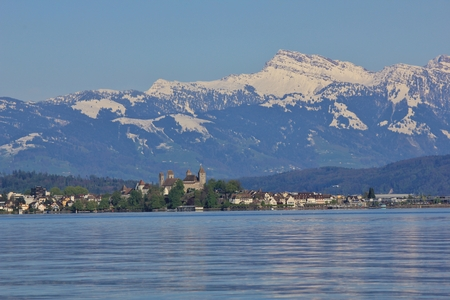 Spring scene at lake Zurichsee. Medieval castle in Rapperswil. Grosser Speer, snow capped mountain.