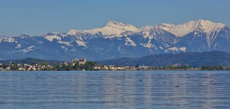 Springtime at lake Zurichsee. Rapperswil and snow capped mountain Grosser Speer.