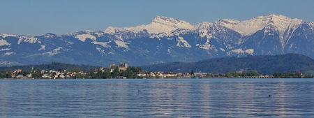 st gallen: Rapperswil on a spring day. Medieval castle, lake Zurichsee and snow capped mountain Grosser Speer. Stock Photo