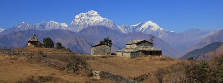 Autumn day in the Himalayas. Seventh highest mountain of the world, Dhaulagiri. Old stone house and shed.