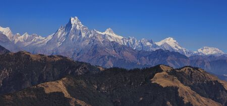 Fish tail mountain Machapuchare and other mountains of the Annapurna range on a autumn day. View from Mohare Danda, Nepal.