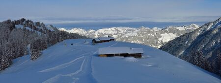 View from mount Hohe Wispile, Gstaad. Snow covered trees and mountains.