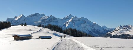 Snow covered mountains Schlauchhorn and Oldenhorn. Winter hiking and sledging trail. Scene near Gstaad, Switzerland.