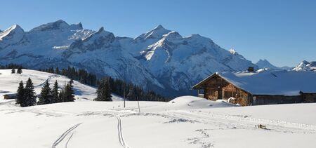 Idyllic winter landscape near Gstaad, Switzerland. Snow covered mountains Schlauchhorn and Oldenhorn.