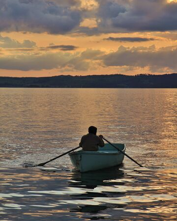 Summer sunset in Ebeltoft, Djursland. Man rowing in a small boat. Stock Photo