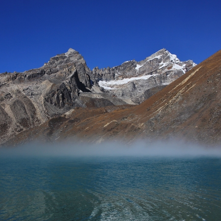 Morning fog over turquoise Lake Gokyo, Nepal. Stock Photo