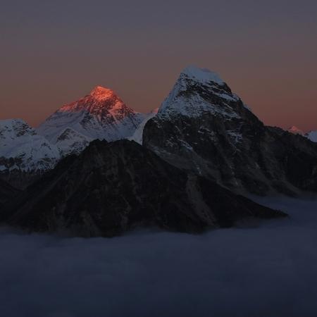 Last sunlight of the day illuminate Mt Everest. Sea of fog.