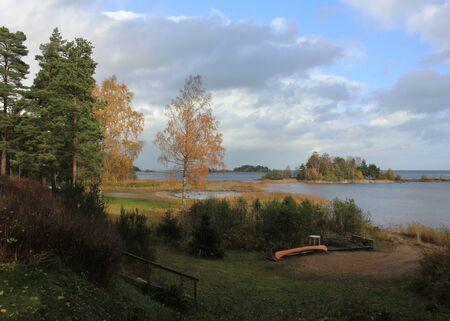 Goldene Bäume und Insel nahe dem Ufer des Sees Vanern, Schweden.