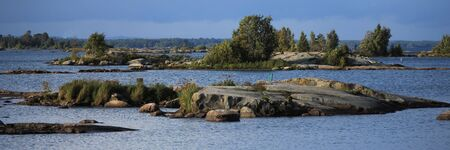 View from a place in Mellerud. Rock formations and small islands covered by trees. Shore of Lake Vanern