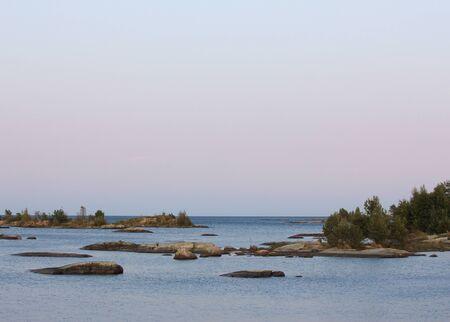 Blue horizon over Lake Vanern. Rock formations and small island at sunset. Standard-Bild