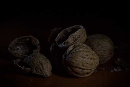 Dramatic looking pile of walnuts and cracked empty shells on a wooden table Stock Photo
