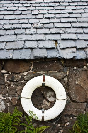 Life-preserver on a wall in a fishermen village - Scotland photo
