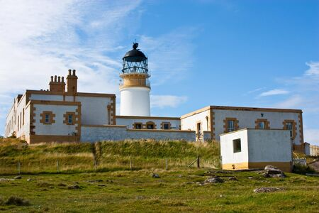 Lighthouse in Sutherland, Scotland, close to cliffs photo