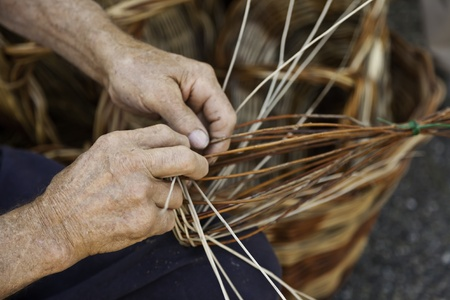 interleaved: Old hands working in a basket costruction Stock Photo