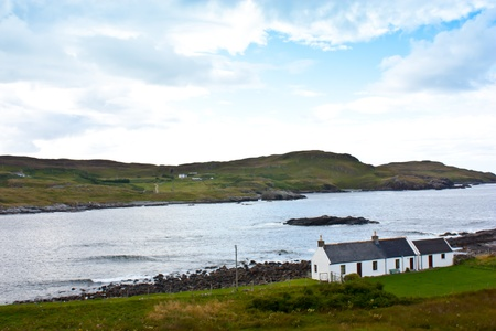 Panorama with a traditional Scottish house in front of a lake. photo