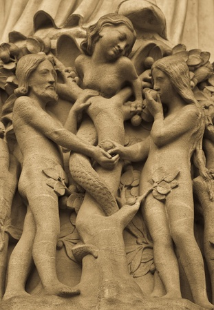 Detail on Notre Dame de Paris Cathedral fachade: Adame, Eve and the forbidden apple Stock Photo