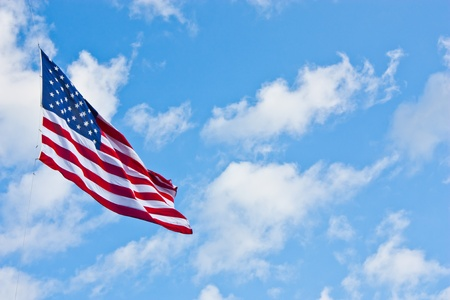 American flag on a blue sky during a windy day