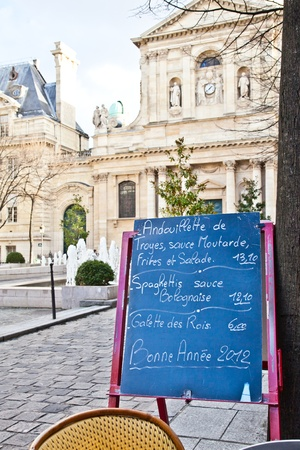 parisian: Black board with a menu restaurant in a tipical traditional square in Paris Editorial