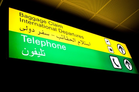 Baggage claim and telephone sign in an international airport in Middle East with Arabic information
