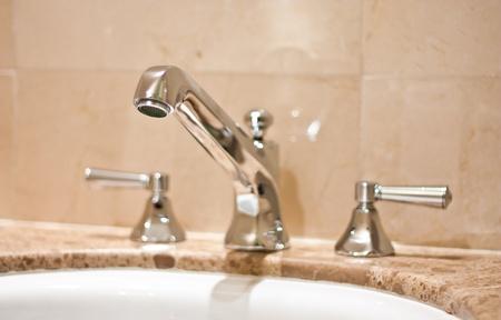 Tap in an Italian luxury hotel, steel on marble photo